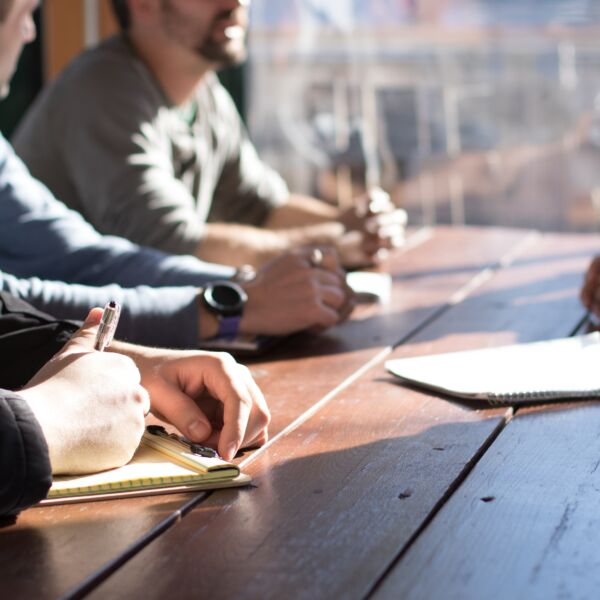 meeting around a table with a man taking notes. PMO set up in 6 steps.
