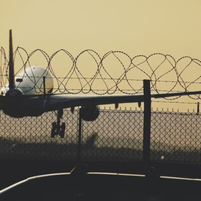 Aeroplane taking off with wire fencing in foreground