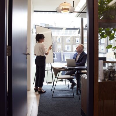Two business people talking in a meeting room. Woman presenting on a whiteboard.