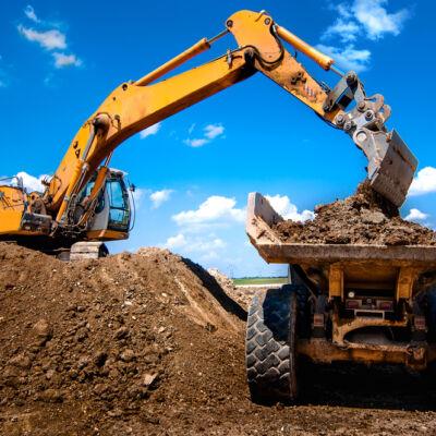 Excavator loading dumper truck tipper in sandpit in highway construction site