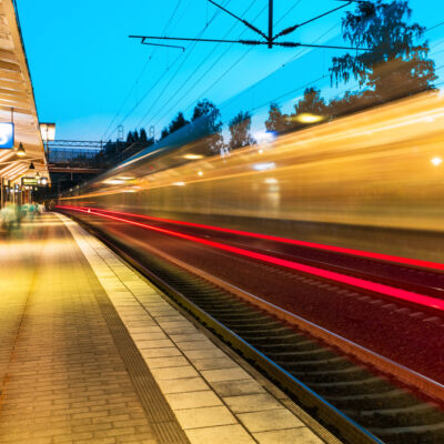 Creative railroad travel and transportation industry business concept: summer evening view of high speed commuter passenger train departing from railway station platform with motion blur effect