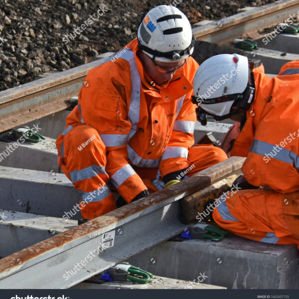2 men in orange hi vis working on the rail tracks